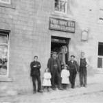 Pictured: Thomas Hope, second from left, outside his draper's shop in Stow with his employees. The two little girls are thought to be his daughters, Ella and Mamie. The photograph was probably taken in the 1920s.   Photograph courtesy of Jean Webber.